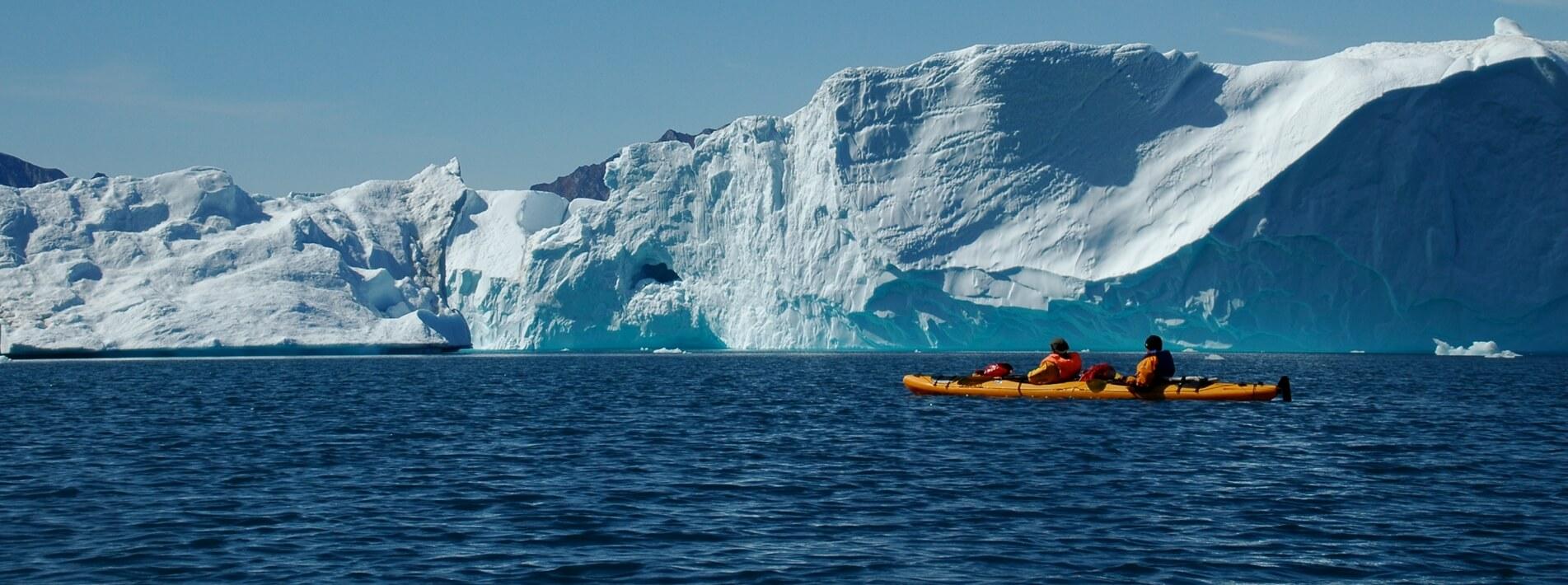 Kajak Fahrer vor einem großen Eisberg