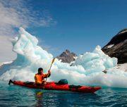 Kajak Fahrer, im Hintergrund ein Eisberg