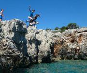 Teilnehmer springen von Felsen