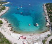 Kajaks am Strand in einer Bucht mit türkisblauem Wasser